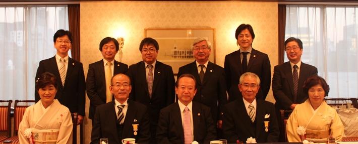 黄綬褒章を受章した原崎正会員(手前左から2人目)と西山雅也会員(同右から2人目)を囲んで